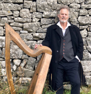 Patrick Ball and harp by stone wall